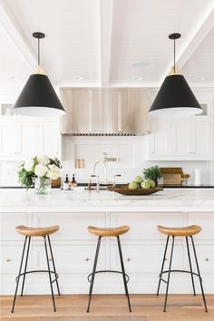 Lit by Rejuvenation Butte Cone Pendants hung from a beadboard ceiling accented with white beams, five sleek wood and island counter stools sit in front of a large white island completed with stacked drawers and a white marble countertop holding a sink with a polished nickel gooseneck deck mount faucet in front of a stainless steel oven range fixed between black quartz countertops.