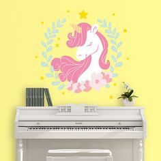 Vinilo decorativo con la imagen de un unicornio entre una corona de flores.  Un diseño de lo más original que puede colocar fácilmente en la pared de tu hogar.