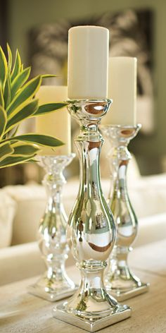 Metal silver candlesticks provide a modern look. Try placing scented candles on top. Shop online now. #LivingSpaces