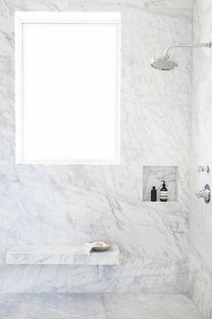 Gorgeous marble clad shower is lined with a floating marble bench placed under a window and next to a square tiled shower niche.