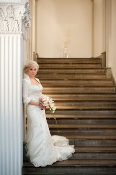 A bride on stairs and holding a bucket.