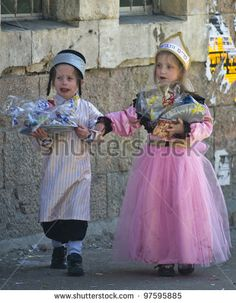 JERUSALEM - MAR. 09 : Ultra Orthodox children holding Mishloach Manot during Purim in Mea Shearim Jerusalem on Mar. 09 2012 , Mishloach Manot is traditional food gifts given during Purim - stock photo