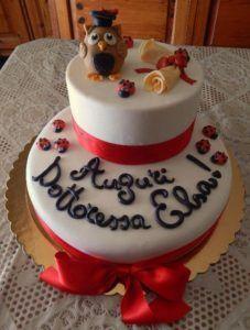 Cake design per torta di laurea a due piani, con scritta, pergamena e gufo laureato in pasta di zucchero