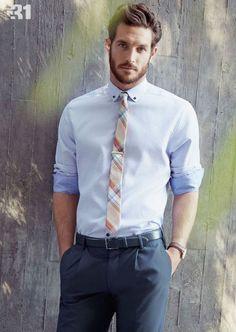 Calça em alfaiataria azul marinho, camisa social azul claro e destaque pra gravata slim quadriculada em cores claras.