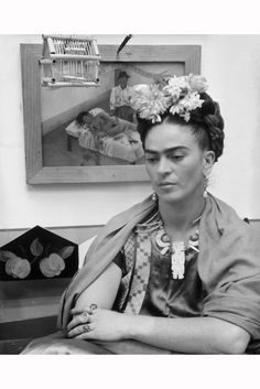 frida-kahlo-1907-1954-sits-with-her-arms-folded-looking-down-in-front-of-one-of-her-paintings-and-a-wooden-bird-cage-she-wears-flowers-in-her-hair-and-a-wooden-necklace-dec-1944.jpg (1136×1700)