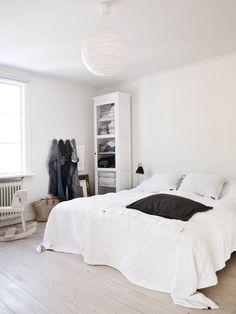 Isossa makuuhuoneessa mahtuu tekemään myös töitä. Valkoinen, lasi-ovinen kaappi on hankittu raumalaisesta Hannas-liikkeestä. Kaapissa säilytetään liinavaatteita, pyyhkeitä, vaatteita ja lehtiä. Valkoinen keinuhevonen on ostettu helsinkiläisestä sisustusliikkeestä. Musta yöpöydän valaisin on Bestliten.