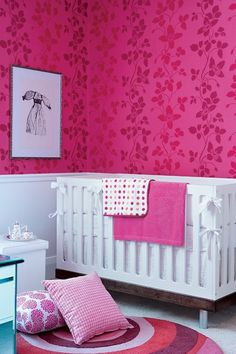 Bold Pink Nursery    Contrast modern furniture with traditional patterns.    A white crib pops against hot-pink wallpaper featuring a fresh twist on damask. Polka dot bedding and a gingham pillow look sweet next to the mod circular rug.