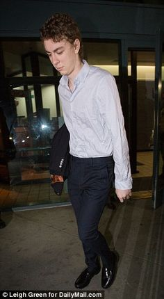Eyes down: Shamed rapist Brock Turner walked out dressed smartly in penny loafers, dress shirt and carrying a blazer under his arm.