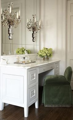 Master bath boasts a built-in make up vanity with 5 drawers topped with statuary marble paired with a moss green velvet tufted vanity chair situated under an inset vanity mirror illuminated by French sconces.