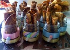 Baby shower brunch idea - French toast sticks housed in baby food jars decorated with ribbon and wee baby bottles. Maple syrup at bottom.