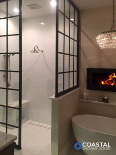 Featured Master Bath: A dream master bathroom with gorgeous walk-in shower featuring two Gridscape shower screens and trench drain in floor. The inset fireplace and chandalier add the perfect touch of modern glam design style above the freestanding tub. #dreambathroom #modernglam #dreamhomes #gridscape #showerdesign #bathroomdesign #interiordesign #bathroominspo #interiorlovers #designinspo #masterbathideas #designtips #interiordesign #designinspiration