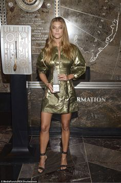 Glamorous in green: The 24-year-old model wowed in an olive zip-up dress that was adorned ...