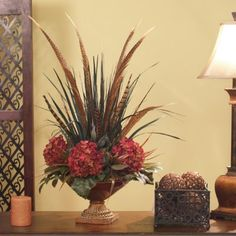 Pheasant Feathers & Hydrangea Floral Design - Add a contemporary look to any home or office with this world market inspired silk floral arrangement. Burgundy hydrangeas, pheasant feathers and grasses are arranged in a red and gold marbled compote! Silk Floral Arrangements, Hortensien Arrangements, Floral Centerpieces, Peony Arrangement, Sunflower Arrangements, Wedding Centerpieces, Faux Flowers, Silk Flowers, Floral Design Classes