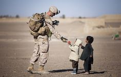 U.S. Marine Lance Cpl. Tom Morton, a 23-year-old team leader with 3rd Platoon, Kilo Company, 3rd Battalion, 3rd Marine Regiment, and native of Nashville, Tenn., hands an Afghan child a toy during a security patrol here
