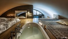 The second floor bedroom, up close to the curved ceiling, serves as a guest bedroom as well as a bathing area, with an in-floor bathtub.