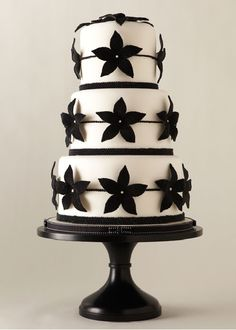 black royal icing flowers with simple piped dot line and edible pearl centers