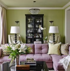 A pink sofa sits in this green, contemporary living space that is full of life and color. Funky, black and white lamps and a bold, green patterned pillows are modern touches. Living Room Decor Purple, Living Room Green, Green Rooms, Living Room Colors, New Living Room, Living Spaces, Purple Sofa, Green Sofa, Style Deco
