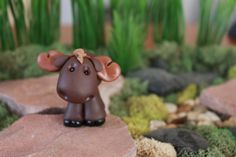 This listing is for one (1) hand sculpted polymer clay moose. He stands approximately 2 inches tall (from the bottom of his hooves to the top of his