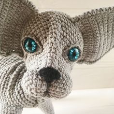 Crochet sphynx grey cat has deep dark blue glass eyes.