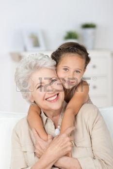 Happy smiling affectionate grandmother and her cute little granddaughter giving each other a loving hug as they smile at the camera photo