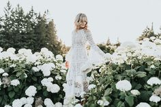 Summer lace wedding dress with bell sleeves in a garden of hydrangeas