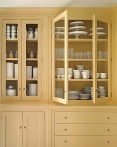 Wanting a cheerful, inviting farmhouse feel, Martha started with Shaker-esque cabinetry, which lends a classic look (and inspired her Maidstone line of Martha Stewart Living Kitchens at the Home Depot). The creamy yellow paint makes this kitchen seem sunn Kitchen And Bath, New Kitchen, Kitchen Yellow, Kitchen Pantry, Kitchen Ideas, Yellow Cupboards, Crockery Cabinet, China Cabinet, Farmhouse Kitchen Cabinets