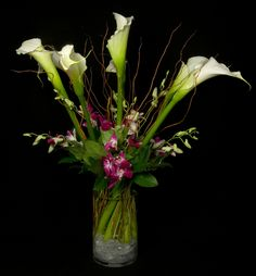 White calla lilies with accents of purple dendrobium orchids.  To view our entire selection please visit us at www.starflor.com #flowers #events #eventdecor