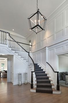 Two story foyer features Restoration Warehouse Hollis Pendant illuminating board and batten walls alongside a sweeping staircase lined with gray stair runner.