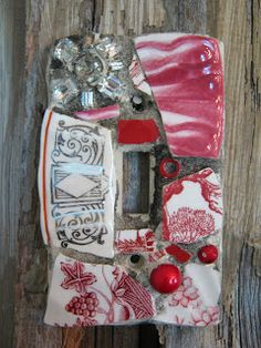 Mosaic single switch plate in reds with rhinestone brooch.