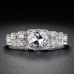 Here is a stunning streamline Art Deco classic, masterfully crafted in platinum, containing a bright and beautiful 1.28 carat old European-cut diamond. The diamond is flanked on either side by three sparkling diamond stair steps embellished with fine milgraining and open gallery work. A sleek and sophisticated original vintage engagement ring from the 1920s.