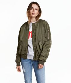 Khaki green. Lightly padded, slightly longer bomber jacket in a generous fit. Zip at front, front pockets with flap, and sleeve pocket with zip. Ribbing at