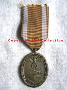 West Wall Medal - obverse with original ribbon. The Deutsches Schutzwall Ehrenzeichen was established on August 2,1939 to award planners, designers and workers who build the Siegfried Line and other defense fortifications on Germany's western border
