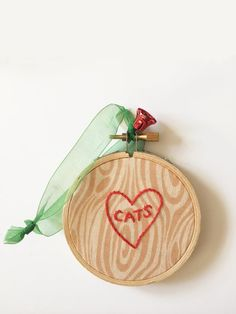 Inspired by the time honored tradition of carving the name of ones true love into a tree, this ornament is the perfect way to declare the love you have for CATS! The perfect gift for anyone who loves cats.  This ornament is one of a kind and features hand drawn and stitched heart with the word  cats  in red thread against a whimsical woodgrain fabric.  Ornament is complete with a ribbon for hanging. Backed with a seasonally neutral fabric, this piece will look lovely no matter where its…