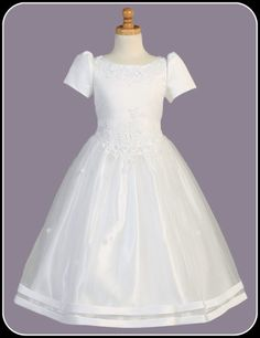 She will be the belle of her day in this graceful white dress that features a satin bodice with rose cut-work appliqué and sheer tulle skirt with rosebuds. Plus size