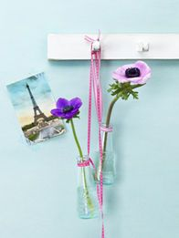 Flaschen-Geister Aperitif-Fläschchen im Retro-Look, kombiniert mit Blumen in Candy-Colours und rosa Textilband, verleihen der simplen Hakenleiste Frühlings-Appeal. Dafür die Fläschchen ausspülen, Hälse fest mit Dekoband umwickeln und verknoten. Zur Hälfte mit Wasser füllen, aufhängen und zum Schluss die Blumen einstecken. Tipp: Nur Florales mit natürlich festem oder drahtverstärktem Stiel wie Anemonen oder Gerbera verwenden.