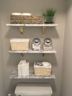 Marble wall-mounted shelves from CB2. wood shelves and toilet paper in a basket.. Farmhouse bathroom remodel ideas #remodeling