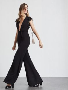 Sometimes a good jumpsuit can make you feel sexier than any dress. The Jolene Jumpsuit is a georgette jumpsuit with a plunging neckline, sheer ruffled sleeves and wide flare legs. Pleated detailing at the bust, fitted nicely in the waist (self belt included if you want to bring it in even more). There's also a slit and hook/zip closure in the back. Made from 100% viscose.