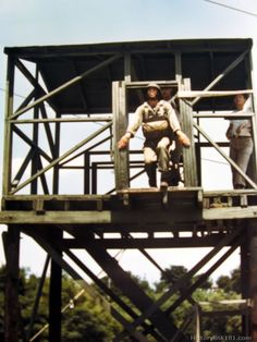 A paratrooper prepares to jump from a mock up tower while instructors look on.