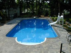 swimming pools winnipeg, inground pools winnipeg, pools winnipeg, This 18 x 36 Roman in-ground has a very grand 10 foot Roman entrance to the pool. Featuring an interlocking patio with a grey Endicott brick edge and retaining walls throughout the yard. These types of features perfectly solve the grade elevation change from the backdoor to the pool but keep it looking clean and grand. This swimming pool looks so good you can almost see it featured in your backyard. Swimming Pools Backyard, Small Swimming Pools, Small Backyard Pools, Garden Pool, Pool Landscaping, Inground Pool Designs, Swimming Pool Designs, Pools Inground, Pool Prices
