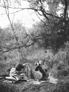 cute engagement photo of couple laying together on a blanket with books | photo: Geneoh Photography