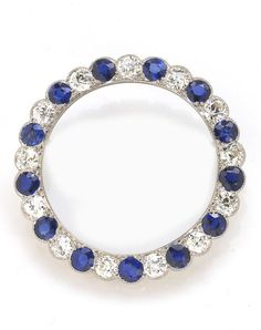 A sapphire and diamond circle brooch  signed D. estimated total sapphire weight: 3.90 carats; estimated total diamond weight: 3.20 carats; mounted in platinum