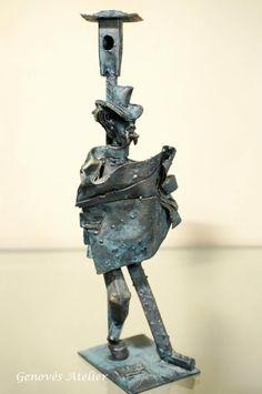 Escultura hecha a mano: Delicada y original pieza de decoración artesanal hecha conhierro forjado a mano bañado en bronce, que representa un tanguero apoyado en una farola leyendo un periódico. Esta firmada MG Medidas Altura 24 cm. base figura 7 cm x 6 cm