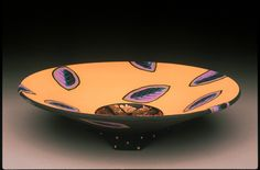 """Small bowl shown in orange.  Clay. Approximate size is 10"""" dia  3"""" h. Layered matte glazes with goldish or copper leaf in center.  Other colors: bright blue, coral, light blue, lavender, teal green, tobacco brown, purple.  Not food safe.  $65."""