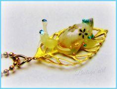 Collier romantique, petite rêverie fantastique, en magnifiant les détails de la nature... collier composé d'un pendentif réalisé avec une feuille dorée squelette en métal sur laquelle évolue un escargot, réalisé avec une véritable coquille d'escargot de rivière et une pâte polymère thermo- fusible.  La coquille est traitée, solidifiée et agrémentée de 3 stickers fleur et de micro- billes de verre bleu-métallisé.