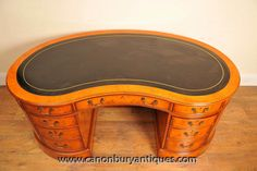 http://canonburyantiques.com/s/desks/kidney-bean-desks/1/  Gorgeous Regency kidney bean desk in satinwood. The kidney bean shape works really well ergonomically on a desk as it wraps around so easy to work at. Great for a home office set up. Large range of other kidney bean desks...