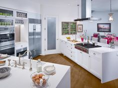 #LGLimitlessDesign and #Contest This minimalistic white kitchen fathers stainless steel appliances throughout, including a stove top and range hood located at the kitchen island. The open nature of the kitchen allows for quick access to the living room area, which incorporates the pink accents that are also used to add pops of color within the kitchen.