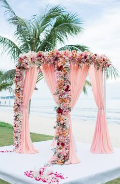 Luxuriously decorated pink arch with blush drapes and blooms of orange, white, red and pink //  We're delighted to share more beautiful wedding decor with you, this time from Chen and Ting's celebration at Panwa House at Cape Panwa in Phuket!
