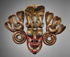 Mask from Sri Lanka, surmounted by coiling cobras and painted in various colors.