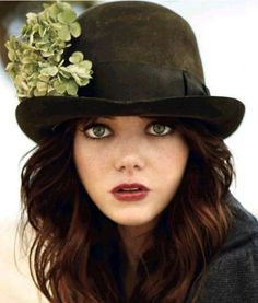 Emma Stone is depicted in a black hat decorated with green clover. She has frightful look and looks at you. She has very bright make-up and dark brown wavy hair. She alsp wear dark grey coat. Plastic Surgery Photos, Celebrity Plastic Surgery, Emma Stone Quotes, Brown Wavy Hair, Actress Emma Stone, Stone Wallpaper, Hd Wallpaper, Wallpapers, Stone Pictures