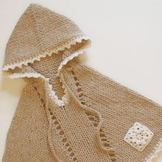 Knit kid poncho with crochet edging and patch